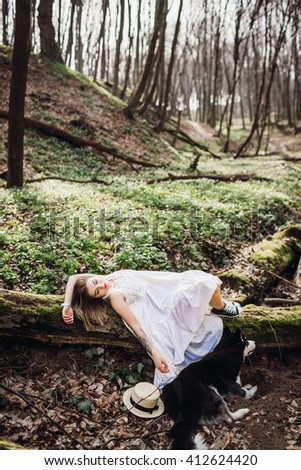 tender girl lying on a tree in the forest - stock photo