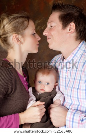 Tender moment of a couple holding their 4 months old baby girl - stock photo