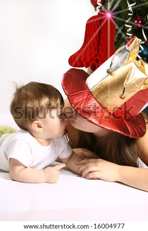 Tender mother kisses small son into Christmas