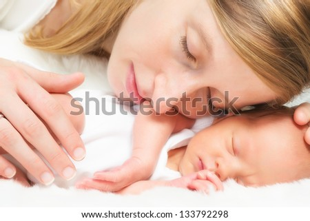 Tender mother lying cheek to cheek with her newborn baby of 11 days old - stock photo