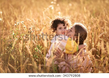 tender mother with daughter on the hands in a wheat field, family in a wheat field On the Sunset