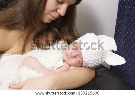 tender mother with sleeping baby at home - stock photo