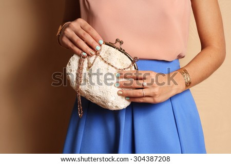 Tender outfit girl in blue skirt holding white little purse . gold jewelry - stock photo
