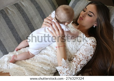 tender photo of beautiful mother with luxurious dark hair and her cute  little baby  - stock photo