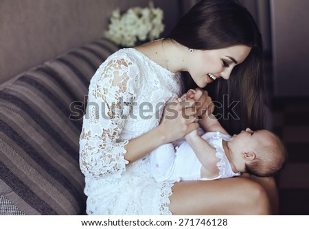 tender photo of beautiful young mother with long dark hair posing with her little adorable baby   - stock photo
