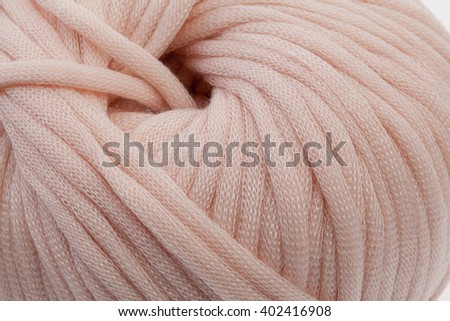 Tender pink wool yarn wrapped in ball. Closeup photo.