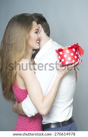 Tender romantic young couple embraces holding red spotted gift, vertical photo - stock photo