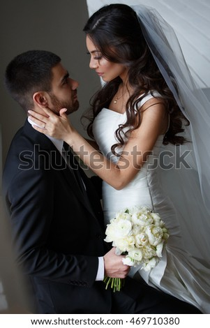 Tender wedding photo session indoor of the elegant bride in a white dress with veil and groom in the classic tuxedo costume