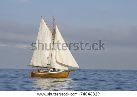 Tender with white sails in the calm sea - stock photo