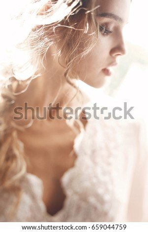 Tender woman in white dress leans her chin to the shoulder