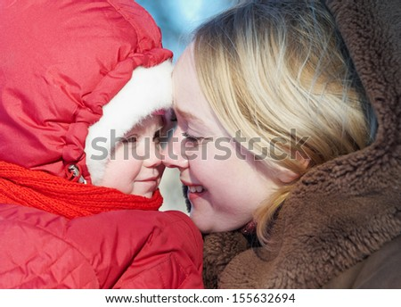 Tender young woman mother with little child daughter in winter - stock photo