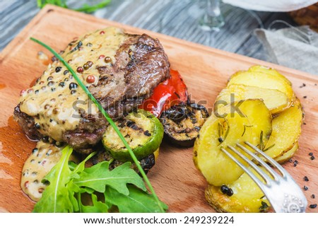 Tenderloin beef steak with spices and fresh herbs served on a wooden board with fresh tomato and roast potatoes - stock photo
