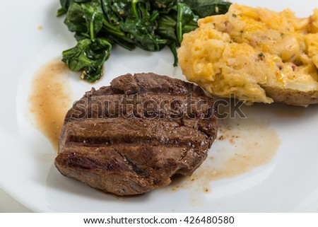 Tenderloin steak grilled to perfection with twice-baked potato and wilted spinach. - stock photo