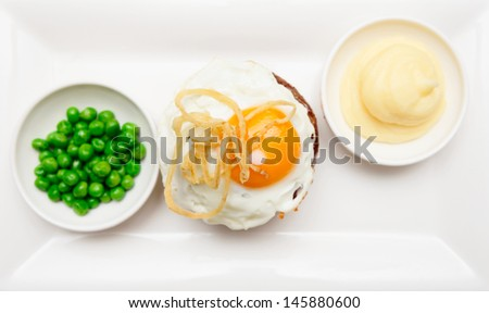 Tenderloin steak with fried egg, potato mash and green pies shot from above - stock photo
