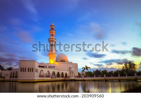 Tengku Nur Zaharah Mosque, Terengganu, Malaysia built on a man-made lake with background of blue sky. Long exposure was used to create running skies effect and silky smooth water on the lake. - stock photo