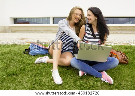 Tennage students sitting on the grass and study together with a laptop - stock photo