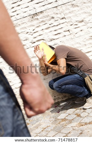 Tennager student with fear at his school (selective focus on the victim) - stock photo