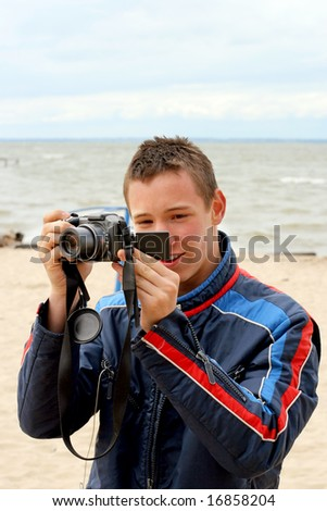 Tennager take a picture on the beach - stock photo