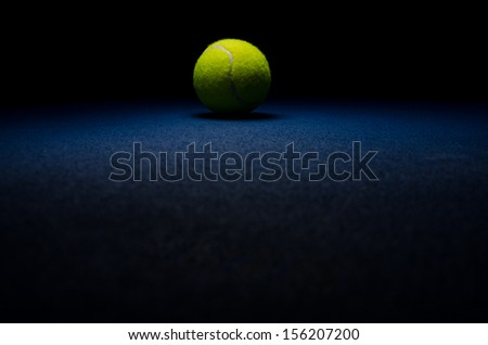 Tennis background - low key centered ball with blue surface - stock photo