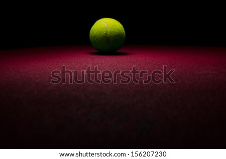 Tennis background - low key centered ball with red surface - stock photo