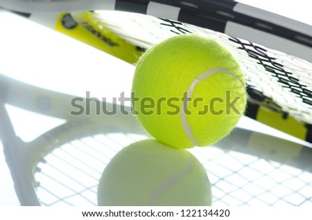 Tennis ball  and a racket on it against a white background
