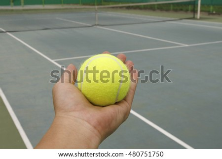 tennis ball and hand on hard court