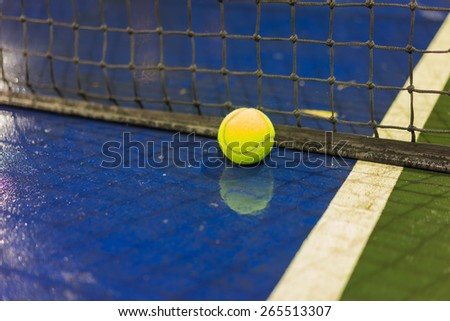 Tennis ball and net on wet ground after raining