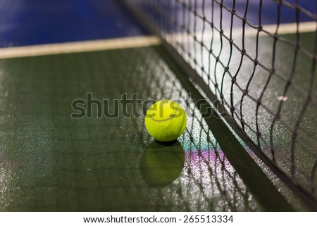 Tennis ball and net on wet ground after raining  - stock photo