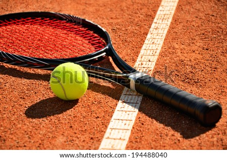 tennis ball and racket is on the carpet court closeup - stock photo