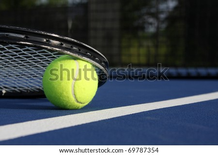 Tennis Ball and Racket on a blue court