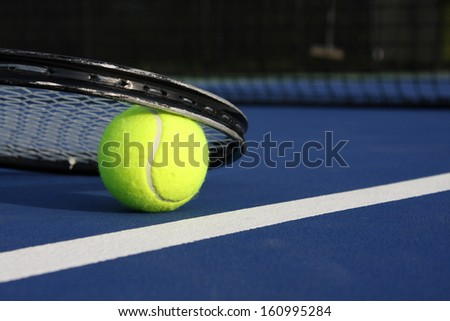 Tennis Ball and Racket on a Blue Court with room for copy - stock photo