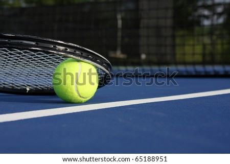 Tennis Ball and Racket on a Blue Modern Court - stock photo
