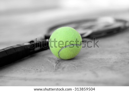 Tennis ball and racket on court - stock photo