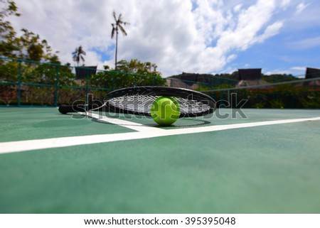 Tennis ball and racket on court close up - stock photo