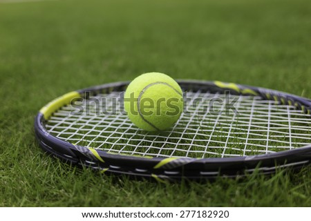 Tennis ball and racket on green grass background