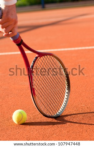 tennis ball and racket on the clay court - stock photo