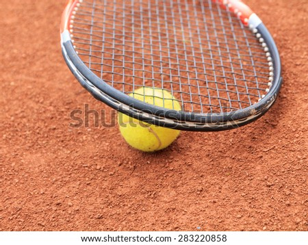 Tennis ball and racket on the clay tennis court - stock photo