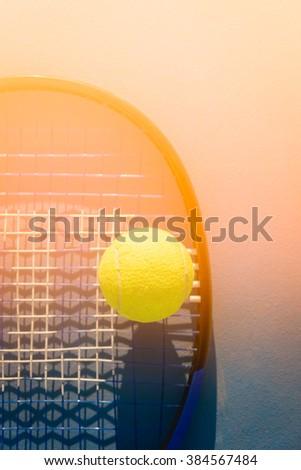 Tennis Ball and Racket. Tennis ball on a tennis court sunset. - stock photo
