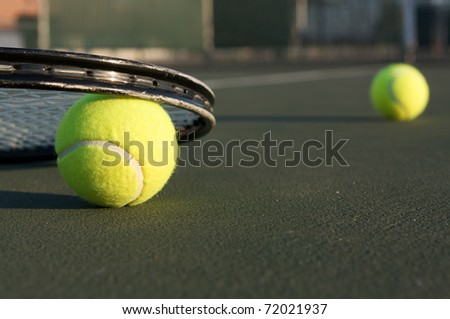 Tennis Ball and Racket with ball in distance - stock photo