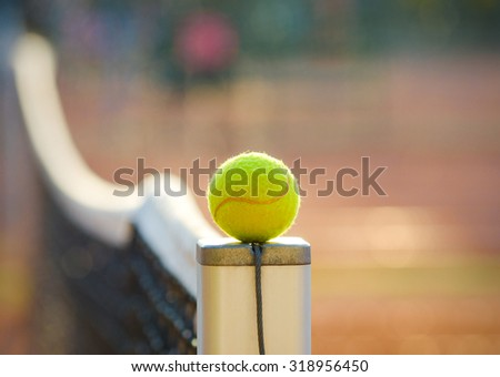Tennis ball close up on a net post with the net flowing on the clay court background suggesting a tennis championship competion or training with soft filters applied - stock photo