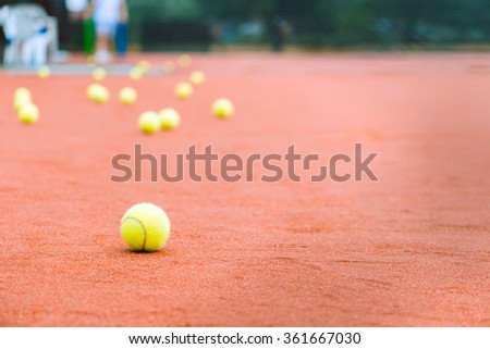 Tennis ball close-up on clay court - stock photo