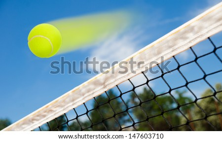 Tennis ball flying fast over a net suggesting a winner point for the match with blue sky - stock photo