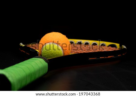 Tennis ball for kids with tennis racket with green grip handle and orange strings on black background - stock photo