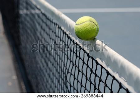 Tennis ball hitting the net - stock photo