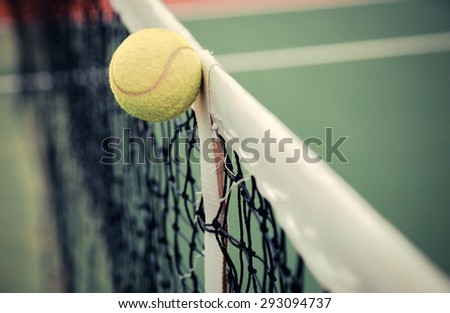 Tennis ball in net at tennis court vintage color