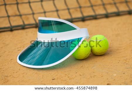 tennis ball in tennis court. Blue Tennis cap. - stock photo