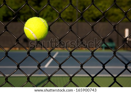 Tennis Ball in the Court Fence with the Court Beyond