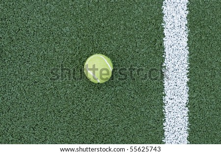 tennis ball lying on a court - stock photo
