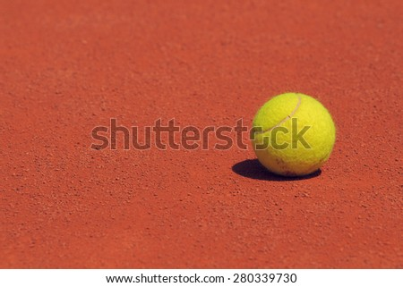 Tennis ball on a clay court. - stock photo