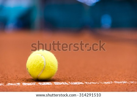 tennis ball on a clay court, close to the fault line - stock photo